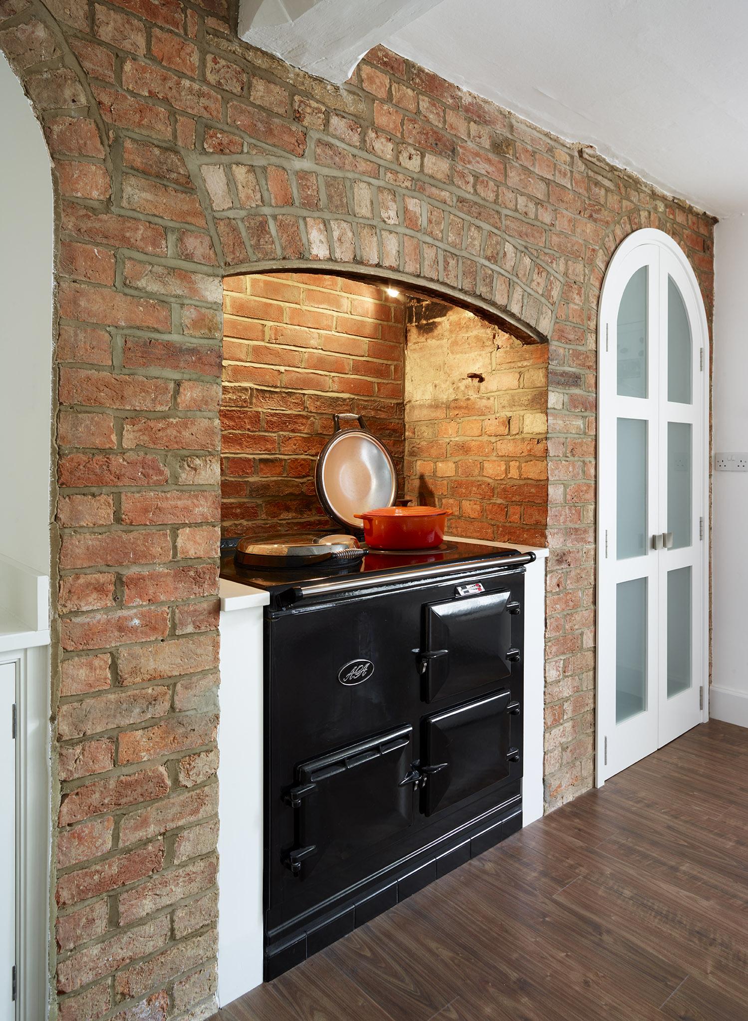 Stoke Goldington - Aga set into existing fireplace within shaker style kitchen